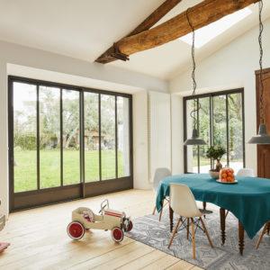Baie vitrée coulissante style atelier dans salon avec poutres