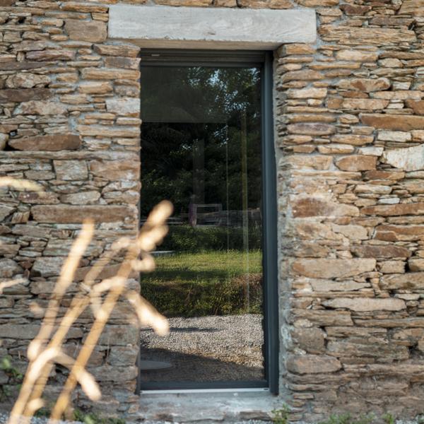 Vitrage fixe en aluminium noir et mur en pierre